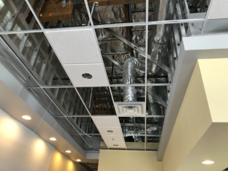 Commercial HVAC system behind an uncovered acoustic ceiling