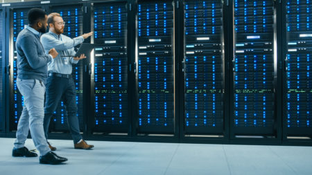 Two data center technicians walking past illuminated server racks.